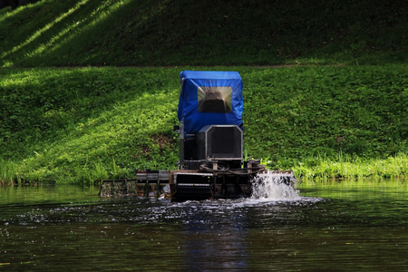 Mini dredger is clearing lake algae in summer day. Eutrophication of White lake in Gatchina, Russia. Stock Photo