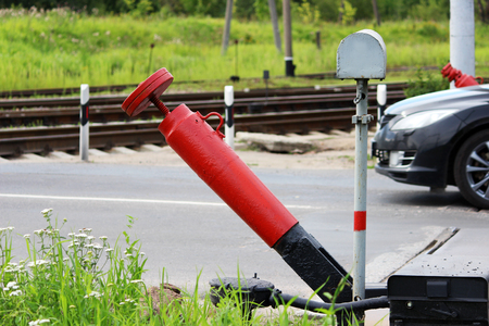Railway crossing, anti-RAM devices. Red crossing fence device that automatically lifts plates on the road, prohibiting the passage of cars when the train approaches.