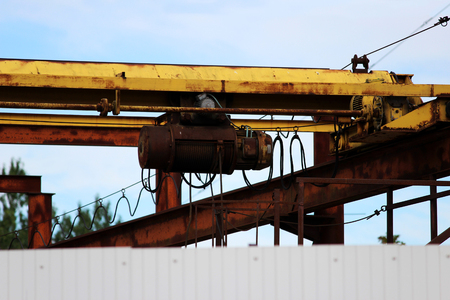 old rusty crane beam in the warehouse under the open sky near the building supermarket for handling operations Stock Photo