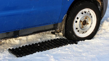 black anti-slip mat of a rectangular shape is placed under the wheel of a low-leveled car after it is stuck in a snowdrift and slips. reportage shooting