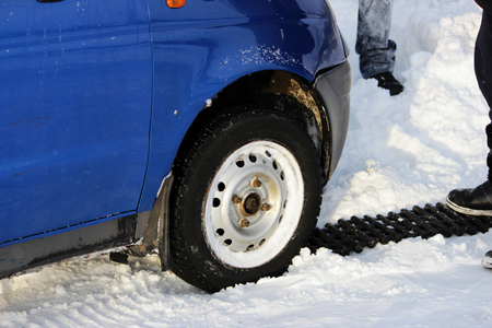 black anti-slip mat of a rectangular shape is placed under the wheel of a low-leveled car after it is stuck in a snowdrift and slips.