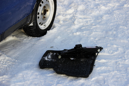 The adjustable jack on the rug on the snow. a blue low-lying car got stuck in a snowdrift. reportage shooting.