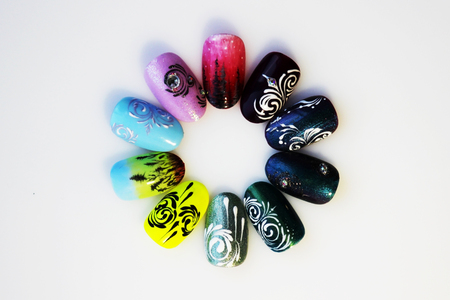 many plastic pink tips for nail extension and training in applying design while training a manicure. trial student work in the form of monograms, flowers and animals, with pasted pastes on a white background Imagens