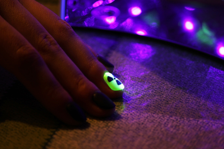 the original manicure in the form of a radioactive danger sign with gel shellac varnish, glows in the dark with ultraviolet light