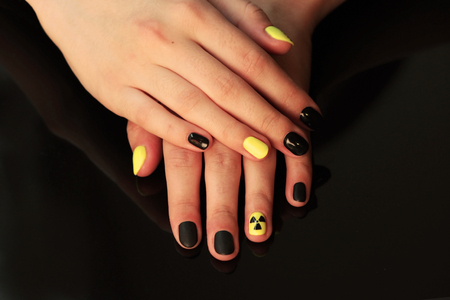 beautiful black-and-yellow manicure with shellac varnish in the form of a sign of radioactive danger. hands of the girl on a black shiny background