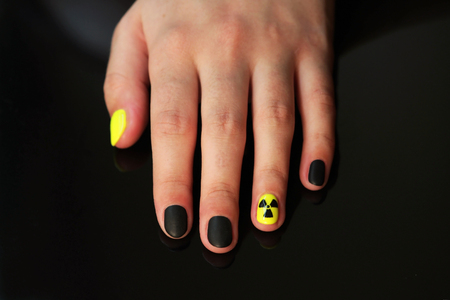 beautiful black-and-yellow manicure with shellac varnish in the form of a sign of radioactive danger. One hand of the girl on a black shiny background
