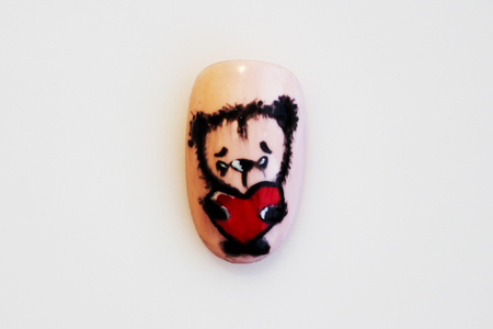 one plastic tip for nail extension and training in applying design while training a manicure on a white background. trial student work in the form of bear cub with red love heart Stock Photo