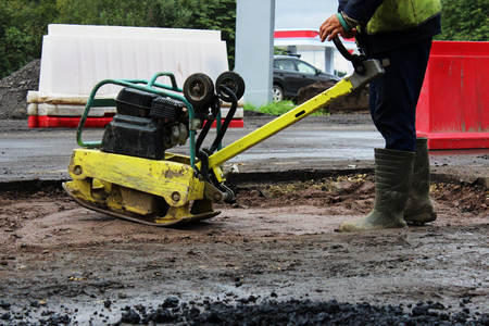 A road construction worker compacts the soil with a compact vibroplate before asphalting a problematic swampy section of the road. Russia, entry in the city of Gatchina.