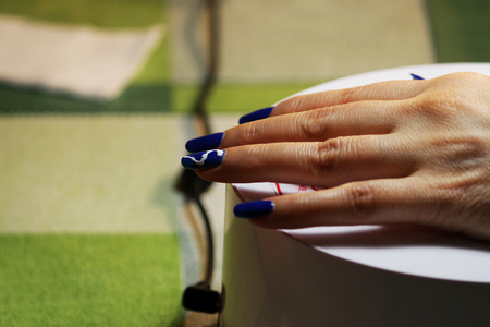 manicure performed by the student. the hand lies on a special ultraviolet lamp. Blue finish with a painted white zipper