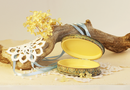 open oval wooden box of hand work, yellow and blue. Dry root of the tree, white knitted napkins, dry hydrangea. Stock Photo