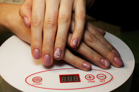 ready manicure shellac. manicure performed by the student. hands lie on a special ultraviolet lamp. Pink matte finish with white monograms