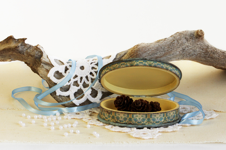 open oval wooden box of hand work, yellow and blue. Dry root of the tree, white knitted napkins, dry hydrangea and cones of larch Stock Photo