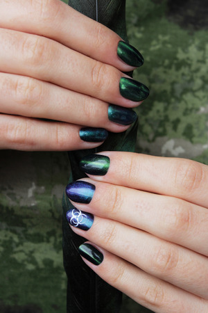 hands of a young girl with green manicure, which shows a sign of biological danger biohazard and black magpie feather. vertical