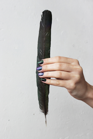 Hand of a young girl with green manicure, which shows a sign of biological danger biohazard and black magpie feather. vertical