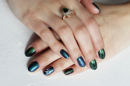hands of a young girl with green manicure, which shows a sign of biological danger biohazard. On one finger - a gold ring with an emerald