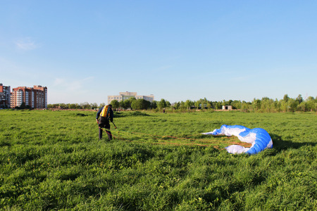 pilot newcomer paraglider is trained on the ground to lift up and hold the blue-white paraplane