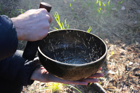 Tibetan bowl with dancing like boiling water in the sunlight in nature as a result of playing on it. Banco de Imagens - 103769256