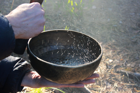 Tibetan bowl with dancing like boiling water in the sunlight in nature as a result of playing on it.