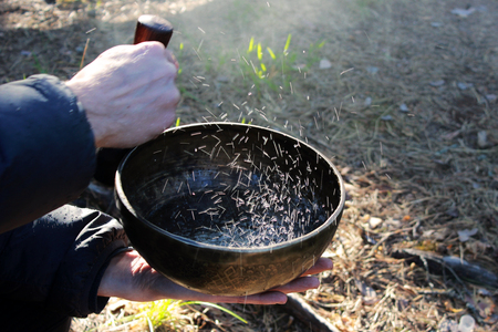 Tibetan bowl with dancing like boiling water in the sunlight in nature as a result of playing on it. Banco de Imagens - 103769402