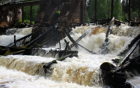 An old dam on the river with stormy water. Leningrad Region, Russia. Stock Photo - 103769327