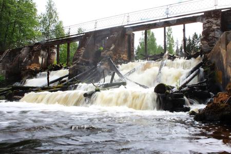 An old dam on the river with stormy water. Leningrad Region, Russia. Stock Photo - 103769329