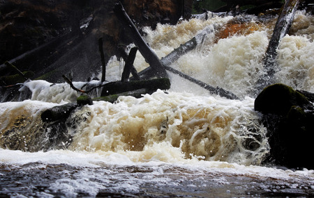 An old dam on the river with stormy water. Leningrad Region, Russia.