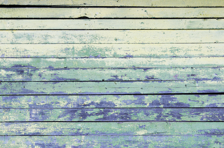 Vintage wood background with peeling yellow and turquoise old flaky paint. wall of an old house.