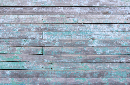 Vintage wood background with peeling turquoise old flaky paint. wall of an old house. Imagens