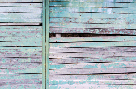Vintage wood background with peeling turquoise old flaky paint. Slanting slit in the wall of a large barn due to skewed boards