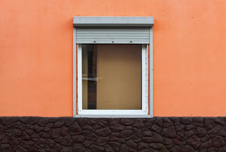 One window in the house is half closed by external shutters. bright orange and brown color of the plaster. Reklamní fotografie - 105579917