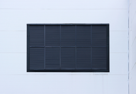 A window in a large industrial shopping center closed with external jalousie in the form of ventilation grilles. light blue background.