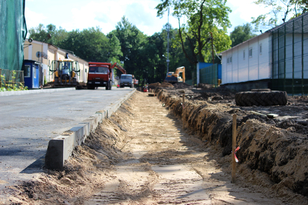 Preparation for the construction of the pavement from the paving slab - sand is poured in the form of a foundation. Stock Photo