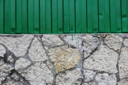 The wall of the building is from a juicy green metal siding and finishes in the form of pieces of stone tiles.