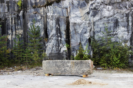 gray natural marble with white streaks in the canyon, deposit, Karelia. A stone bar in the form of a antivandal bench rests on wooden planks