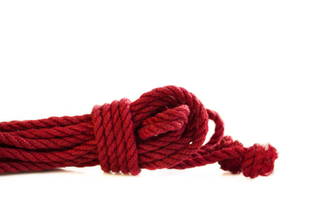 One skein of jute rope six millimeters for Japanese bondage and shibari, painted in red on a white background. Professionally knitted hank Фото со стока - 111791892