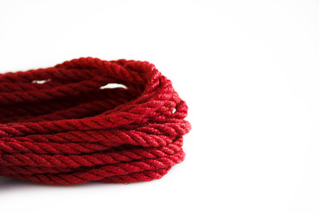 One skein of jute rope six millimeters for Japanese bondage and shibari, painted in red on a white background. 写真素材
