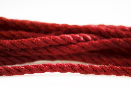 One skein of jute rope six millimeters for Japanese bondage and shibari, painted in red on a white background. Professionally knitted hank.