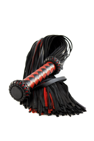 Red-black floger with a patterned handle and leather tails. vertical photo on white background.concept of pleasure from pain.