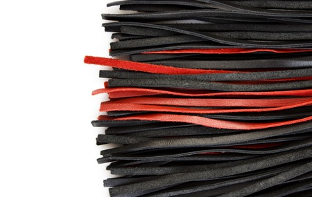 Red-black floger with leather tails on white background.concept of pleasure from pain. Stock Photo