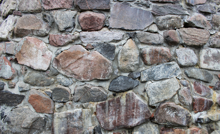 A stone wall with artistic veins. Many cobblestones glued with cement. Karelia.