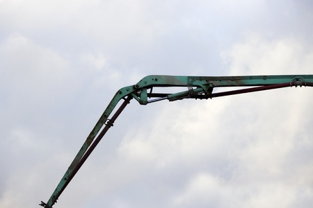 The device of a turquoise loader on the railway. Hydraulic system against the sky.
