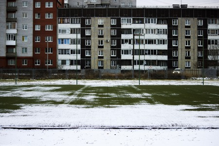 football field in the city courtyard and a panel house after the first snow fell.