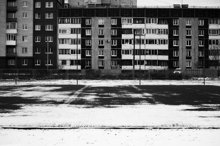 football field in the city courtyard and a panel house after the first snow fell. Black and white Stock Photo