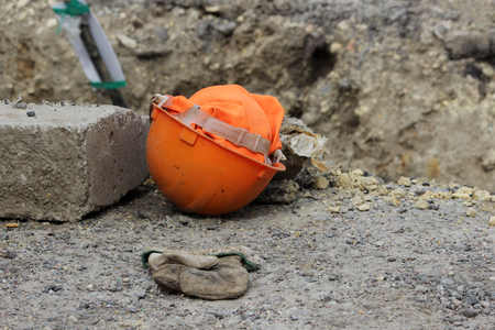 orange hard hat and work glove. working reportage, Russia. elimination of the accident at the water utility.