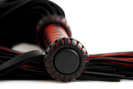 Red-black floger with a patterned handle and leather tails on white background.concept of pleasure from pain.