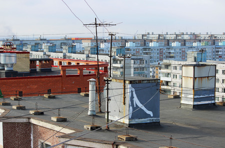 view from the flat roof of a multistory building covered with ruberoid, railing. column with electrical wires, television antenna and ventilation pipe. view of the city of Arkhangelsk Stock Photo