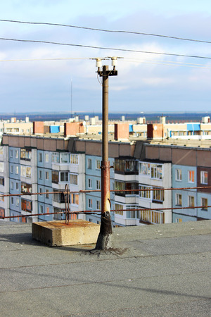 view from the flat roof of a multistory building covered with ruberoid, railing. column with electrical wires. view of the city of Arkhangelsk Stock Photo
