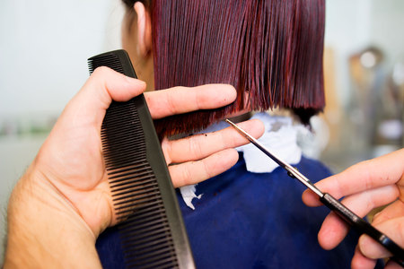 Redhead young woman getting haircut by man hairdresser, which does a bob hairstyle after dyeing