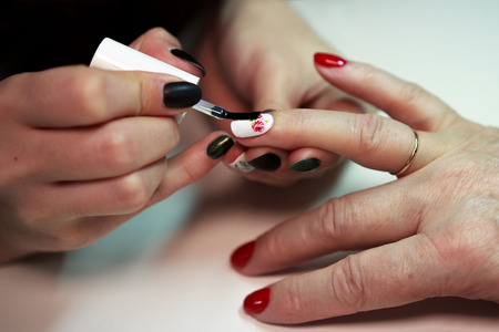 master glues a decal with a rose on the nails on a red and white lacquer manicure. reporting shooting