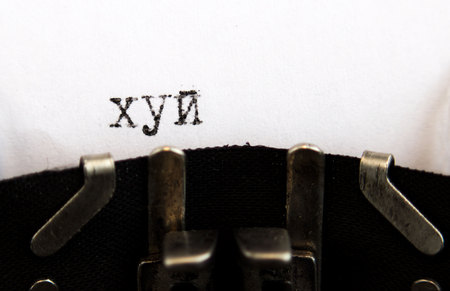 Old soviet typewriter close up. Filled in it blank sheet of paper with the word dick written in Russian. Macro.